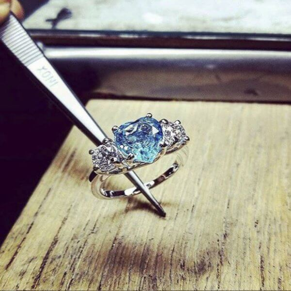 Trilogy ring with blue stone and diamonds